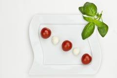 Tomato Mozzarella. Mozzarella balls with cherry tomatoes on a white plate Royalty Free Stock Image
