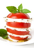 Tomato and mozzarella. Slices decorated with basil leaves on a plate and white background Stock Photos