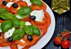 Caprese salad. Classic caprese salad. Italian traditional caprese salad ingredients. Mediterranean food. Caprese salad Tomato and mozzarella with basil leaves Stock Image