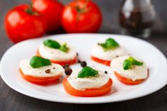 Tomato and mozzarella with basil leaves Stock Images