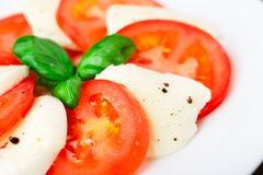 Tomato and mozzarella with basil leaves Royalty Free Stock Photography