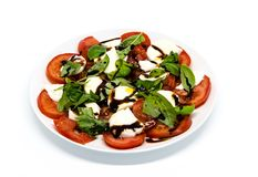 Tomato and mozzarella with basil leaves on a plate Royalty Free Stock Photos