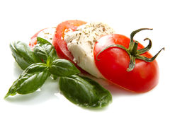 Tomato and mozzarella with basil leaves on white Stock Images