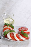 Tomato and mozzarella with basil leaves Stock Image
