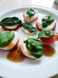 Tomato, mozzarella and basil snack. Healthy snack with tomatoes, mozzarella cheese, basil and balsamic vinegar stock photos