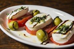 Tomato and mozzarella cheese with balsamico. Plate of a fresh tomato and mozzarella cheese with balsamic0 stock image