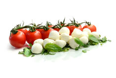 Tomato and Mozzarella II. Studio macro of ripe tomatoes and mozzarella balls garnished with chopped basil. Copy space Stock Image