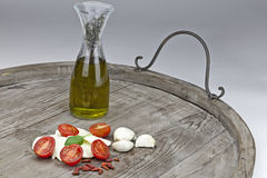 Tomato and mozzarella with olive oil. Halved tomatoes with slices of mozzarella and flavored olive oil, garlic and peppers Royalty Free Stock Photo