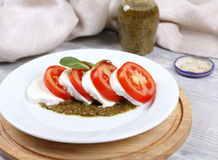 Tomato, mozzarella and pesto. Fresh salad from tomatoes with cheese a mozzarella and pesto sauce Stock Photography