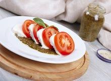 Tomato, mozzarella and pesto. Fresh salad from tomatoes with cheese a mozzarella and pesto sautse Royalty Free Stock Images