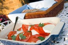 Tomato and mozzarella salad with ciabatta. Tomato, mozzarella and basil salad on an outdoor table with basket of freshly made ciabatta bread in the background Stock Image