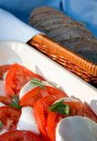 Tomato and mozzarella salad with ciabatta. Tomato, mozzarella and basil salad on an outdoor table with basket of freshly made ciabatta bread in the background Royalty Free Stock Images