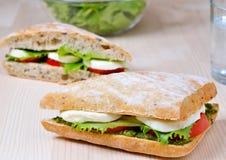 Tomato Mozzarella Sandwich. Closeup of a fresh sandwich with mozzarella, tomatoes and pesto Stock Image