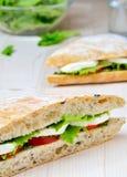 Tomato Mozzarella Sandwich. Closeup of a fresh sandwich with mozzarella, tomatoes and pesto Royalty Free Stock Photo