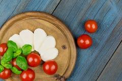 Tomato mozzarella slice basil wood Stock Photos