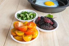 Tomato, mulberry side dish ingredient and fried egg in pan Stock Photography