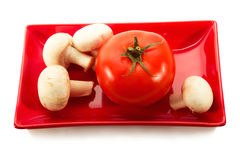 Tomato and mushrooms on a plate. Tomatoes and mushrooms on a red plate isolated on white background Royalty Free Stock Photos
