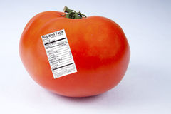 Tomato with Nutrition Label. Red, ripe tomato with nutirition fact label attached Royalty Free Stock Photo