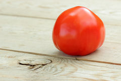 Tomato. One red tomato on a wooden table Royalty Free Stock Photo