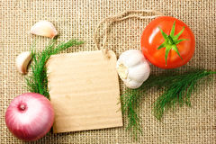 Tomato, onion and garlic with cardboard price tag on sacking bac Royalty Free Stock Photos