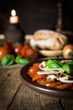 Tomato and onion salad on a old wooden table, Candlelight in the Royalty Free Stock Photography