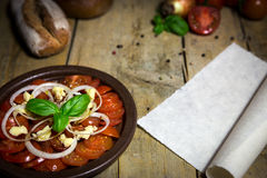 Tomato and onion salad on a old wooden table, parchment scroll w Royalty Free Stock Photos