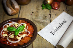 Tomato and onion salad on a old wooden table, scroll with word e Royalty Free Stock Photo