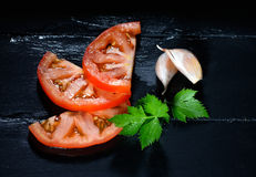 Tomato with Parsley and Garlic Cloves. Healthy and Organic Foods. Healthy tomato slices with parsley and garlic cloves. Healthy and organic foods Royalty Free Stock Images