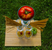 Tomato and Pasta on Display 1. This is a creative image of tomatoes, pasta, and wine classes.The perspective is very interesting royalty free stock photos