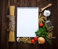 Tomato, pasta, garlic, parsley and empty notebook Stock Image