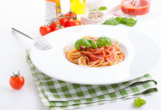 Tomato pasta spaghetti with fresh tomatoes, basil, italian herbs and olive oil in a white bowl on a white wooden background Royalty Free Stock Images