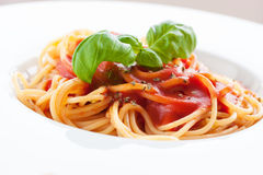 Tomato pasta spaghetti with fresh tomatoes, basil, italian herbs and olive oil in a white bowl Stock Photos