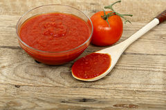 Tomato paste. Bowl of tomato paste on wooden surface Royalty Free Stock Photography