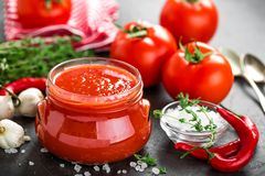 Tomato paste, puree in glass jar and fresh tomatos on dark background Royalty Free Stock Photo