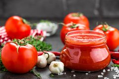 Tomato paste, puree in glass jar and fresh tomatos on dark background Stock Images