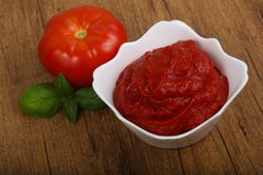 Tomato paste. With basil leaves Stock Photo