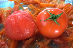 Tomato peeled and unpeeled. Whole peeled tomato and skins on plate Royalty Free Stock Image