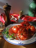 Tomato and pepper mill still life. Tomatoes and pepper mill in the kitchen lighted by the sunset stock photo