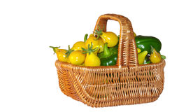 Tomato and peppers in a basket. Green peppers and yellow cherry tomatoes in a basket stock image
