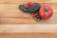Tomato and Peppers on a Cutting Board. A fresh tomatoe, poblano, and some small chilis seen from above on a wooden cutting board in the upper right Royalty Free Stock Photography
