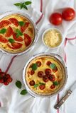 Tomato pies with basil leaves, chicken ans cheese on white tablecloth. Homemade french quiche. Top view stock photo