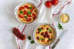 Tomato pies with basil leaves, chicken ans cheese on white tablecloth. Homemade french quiche. Top view, copy space stock image