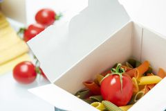Tomato placed in a color pasta box royalty free stock photos