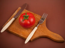 Tomato on plate. One tomato with fork and knife on plate Royalty Free Stock Photography
