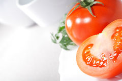 Tomato on plate. Red tomato on white plate Stock Photo