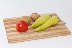 Tomato potato and green paprika on the wooden board Stock Images
