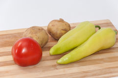 Tomato potato and green paprika on the wooden board Royalty Free Stock Photo