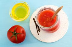 Tomato puree in a glass jar and olive oil for preparing homemade face and hair mask. Ingredients of DIY cosmetics. Stock Photos