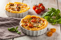 Tomato quiche. Quiche with cherry tomatoes on a rustic wooden table Stock Photos