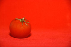 Tomato on Red. Red tomato with stalk  on red background Stock Photography
